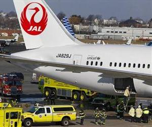 A Japan Airlines Boeing 787 Dreamliner jet is surrounded by emergency vehicles while parked at a terminal E gate at Logan Airport in Boston as a fire chief looks into the cargo hold, Jan. 7, 2013.
