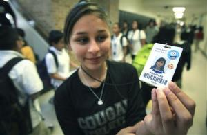 Student Tira Starr shows her ID badge as students change classes in San Antonio, Texas.