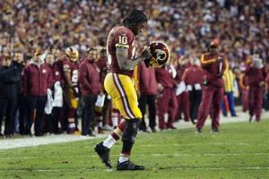 In this Jan. 6 photo, Washington Redskins quarterback Robert Griffin III returns to the huddle after hurting his right knee in the first quarter.