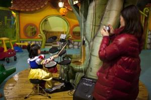 A parent takes photos of her daughter playing the drums at a children's play area in a shopping mall in Beijing.