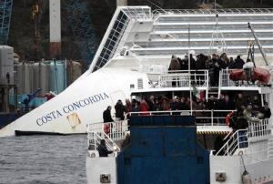 Relatives of the 32 victims of the Costa Concordia shipwreck aboard a ferry approach the Costa Concordia shipwreck off Isola del Giglio, Italy, Sunday, Jan. 13, 2013.