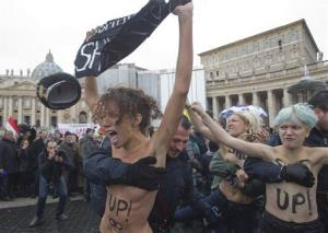 Italian police officers stop a group of four women who went topless to protest the Vatican's opposition to gay marriage, in St. Peter's Square at the Vatican, Sunday, Jan. 13, 2013.
