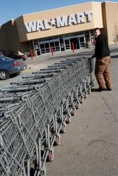In this Monday, Feb. 16, 2009 file photo Walmart employee Sean Blais moves shopping carts in the parking lot of the Walmart store in Weymouth, Mass.