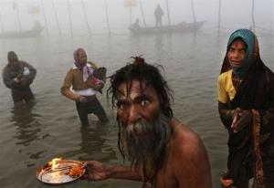An Indian Hindu holy man performs morning prayers for devotees at Sangam, the confluence of the holy rivers Ganges and Yamuna and mythical Saraswati at the Maha Kumbh Mela.