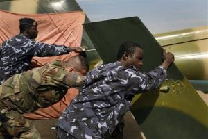 Malian soldiers, foreground and rear, helped by French troops, push a broken helicopter out of a hangar to make room for incoming troops  at Bamako's airport on Tuesday.