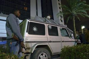 In this Jan. 12, 2013, photo, an armed guard stands next to the armored car of the Italian Consul, Guido De Sanctis, that was fired on as he left the consulate on Saturday in Benghazi, Libya.