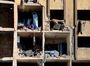 In this photo released by the Syrian official news agency SANA, Syrians stand in the rubble of the damaged university building in Aleppo Tuesday.