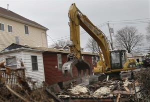 A home that was damaged by Superstorm Sandy is demolished in the Staten Island borough of New York Monday, Jan. 14, 2013.