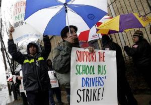 Bus drivers and supporters walk a picket line in front of a bus depot in New York, Wednesday, Jan. 16, 2013.