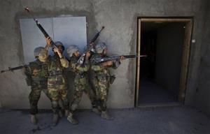 In this Friday, April 23, 2010 file photo, Afghan National Army recruits practice a house clearing during training exercises in Kabul, Afghanistan.
