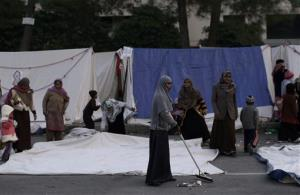 A supporter of Pakistani Sunni Muslim cleric Tahir-ul-Qadri, cleans the ground in front of the tents where she and others are camping near the parliament, during an anti-government rally in Islamabad, Pakistan, Thursday, Jan. 17, 2013. Pakistan's anti-corruption chief refused a Supreme Court order to arrest the prime minister in...