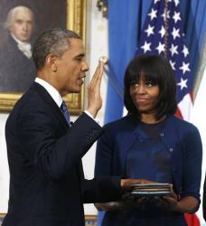 President Obama is officially sworn-in by Chief Justice John Roberts in the Blue Room, Sunday Jan. 20, 2013, as first lady Michelle Obama holds the Robinson Family Bible.