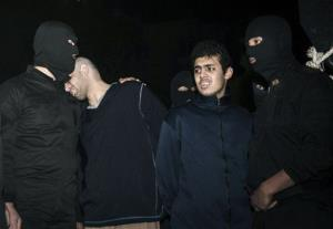 Alireza Mafiha, second left, leans his head on the shoulder of a security officer moments before his execution along with Mohammad Ali Sarvari, second right, in Tehran, Iran, Sunday, Jan. 20, 2013.