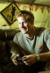 Prince Harry smiles as he plays computer games with his fellow Apache Helicopter crew in Afghanistan.