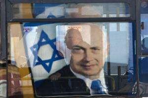 Election campaign billboard of Israeli Prime Minister and Likud Party leader Benjamin Netanyahu is reflected on a bus window in Givataim, Israel, Sunday, Jan. 20, 2013.