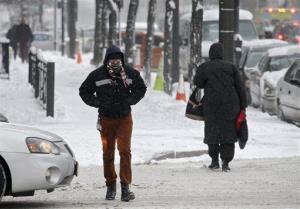 A pedestrian crosses a downtown Cleveland street in wind-blown snow Tuesday, Jan. 22, 2013.