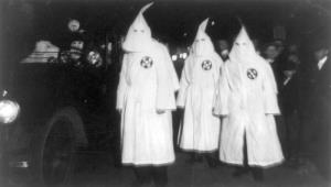 Three Ku Klux Klan members standing beside automobile driven by Klan members at a Ku Klux Klan parade through counties in Northern Virginia bordering on the District of Columbia