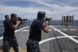 In this Oct. 12, 2012 photo, sailors participate in M4 rifle small arms certification on the flight deck onboard the USS Underwood in international waters near Panama.