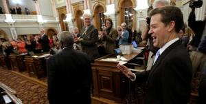 Kansas Gov. Sam Brownback greets lawmakers as he enters the house chambers to deliver his State of the State address Tuesday, Jan. 15, 2013, at the Statehouse in Topeka, Kan.