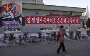 "A woman walks by a board which reads Forward to Final Victory under Leadership of Great Party,"" left, in Pyongyang, North Korea, Friday, Jan. 25, 2013."
