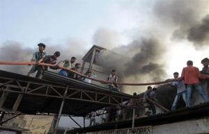 Bangladeshi firefighters and volunteers work to douse a fire at a two-story garment factory in Dhaka, Bangladesh, Jan. 26, 2013.