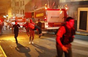 A man carries an injured man, victim of a fire at the Kiss club in Santa Maria, Brazil, early Sunday, Jan. 27, 2013.