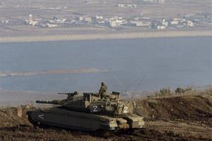 An Israeli soldier on top of a tank overlooking the Syrian village of Bariqa, close to the Israel-Syria border.