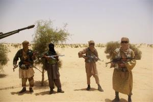 In this April 24, 2012 photo, fighters from the Islamist group Ansar Dine stand guard during a hostage handover in the desert outside Timbuktu, Mali.