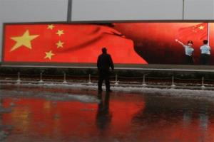 In this Sunday, Nov. 4, 2012 file, a Chinese man stands near a screen displaying the Chinese national flag.