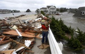 In this Oct. 30, 2012 file photo, Brian Hajeski, 41, reacts as he looks at debris of a home that washed up on to the Mantoloking Bridge after Superstorm Sandy rolled through in Mantoloking, NJ.