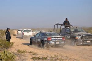 Mexican state and federal police drive along a dirt road leading to a ranch near the town of Mina, where numerous bodies have been found dumped in a well.