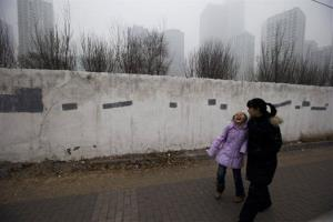 A child laughs as she passes by a smog-shrouded residential district in Beijing Tuesday, Jan. 29, 2013.