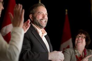 New Democratic Party leader Thomas Mulcair, center, receives applause at a party caucus meeting in Toronto on Sunday, March 25, 2012.