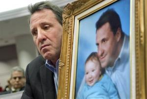 Neil Heslin, holding a picture of himself with his son Jesse, testifies at the Legislative Office Building in Hartford, Conn., Monday, Jan. 28, 2013