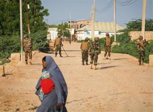 A Somali woman (not the one in question) crosses a street while soldiers of the Djiboutian Contingent serving with the African Union Mission in Somalia (AMISOM) stand guard.