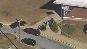 In this image made from video and released by WSB-TV, authorities investigate the scene of a school shooting in Atlanta.