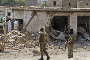 Pakistani men, left, check the damage caused by a car bomb explosion in the troubled Khyber Pakhtunkhwa province bordering Afghanistan, Saturday, Oct. 13, 2012.