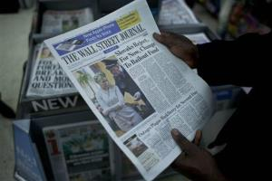 A worker poses for photographs by holding a copy of Wednesday's Wall Street Journal newspaper above a stand with stacks of other newspapers at Victoria train station in London, Oct. 12, 2011.