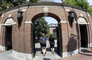 Pedestrians walk through a gate on the campus of Harvard University in Cambridge, Mass.