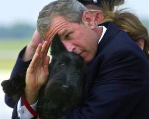 In this June 25, 2001, file photo, President Bush does his best to salute while holding his dog Barney.