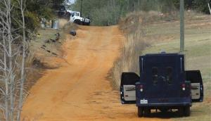 Police vehicles are staged near where a gunman has positioned himself below ground with a child hostage, in Midland City, Ala. on Wednesday Jan. 30, 2013.