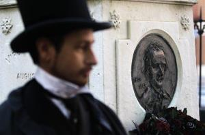 A man in a period costume stands in front of writer Edgar Allen Poe's grave in Baltimore, Friday, Oct. 7, 2011, after a wreath-laying ceremony to commemorate the 162nd anniversary of Poe's death.
