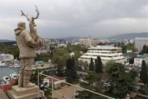 An old Soviet style statue of a reindeer breeder, left, is seen over the Black Sea resort of Sochi, southern Russia. Sochi will host the 2014 Winter Olympics.