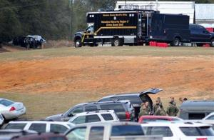 Federal and local law enforcement officers gather at their trucks after the hostage crisis ended in Midland City, Alabama.
