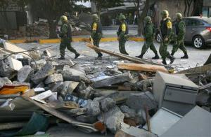 Soldiers patrol next to debris caused by an explosion at the state-owned oil company PEMEX office complex in Mexico City, Friday Feb. 1, 2013. .
