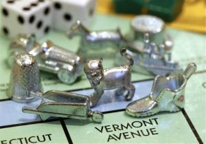 The newest Monopoly token, a cat, center, rests on a Boardwalk deed next to other tokens still in use at Hasbro Inc. headquarters, in Pawtucket, RI, Tuesday, Feb. 5, 2013.