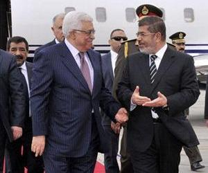 Palestinian President Mahmoud Abbas, left, walks with Egyptian President Mohammed Morsi following Abbas' arrival in Cairo, Egypt, for the Organization of Islamic Cooperation summit, Feb. 5, 2013.