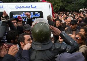 A riot police officer salutes the ambulance carrying the body of Chokri Belaid  after he was shot to death in Tunis, Wednesday, Feb.6, 2013.