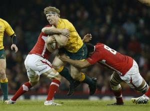 Australia's David Pocock, center, is tackled by Wales' Toby Faletau, right, during the international rugby union match between Wales and Australia at the Millennium Stadium in Cardiff, Dec. 1, 2012.