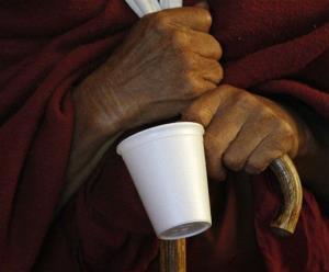 A man holds a Styrofoam cup.
